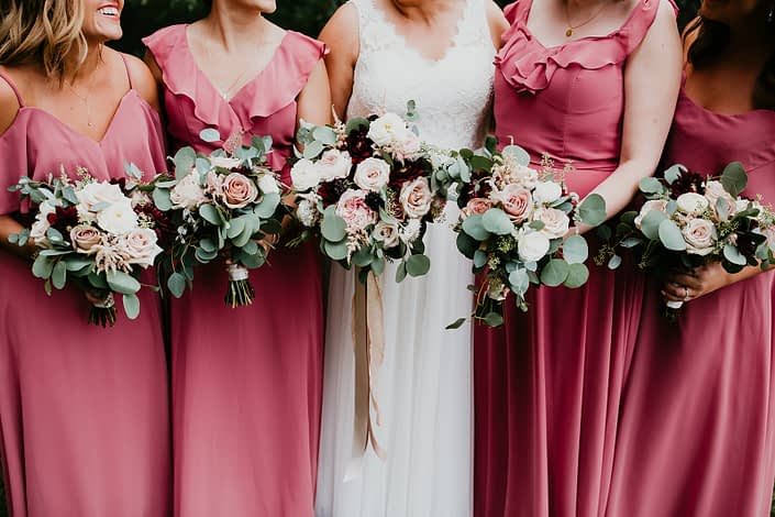 Bride standing alongside bridesmaids wearing pink berry floor length dresses and holding bouquets designed with burgundy dahlias, white ranunculus, roses, astilbe and eucalyptus.