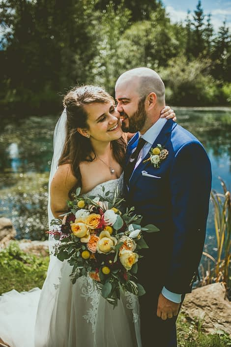 Mustard Yellow Pine and Pond Wedding - Bride and Groom, Bianca and Matt with bridal bouquet featuring golden mustard roses, Juliet garden roses, white ranunculus, Caramel antike garden roses, plum dahlias, craspedia, red astilbe, olive branches and eucalyptus.