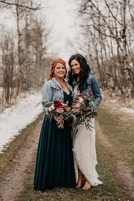 Rustic Boho Chic Wedding - Bride wearing ivory lace dress and jean jacket holding bridal bouquet made of king protea, red peonies, pink roses, plum scabiosa, panda anenome, and eucalyptus greenery standing next to her bridesmaid who is holding a bouquet made of red peony, blush and pink roses, and eucalyptus greenery.