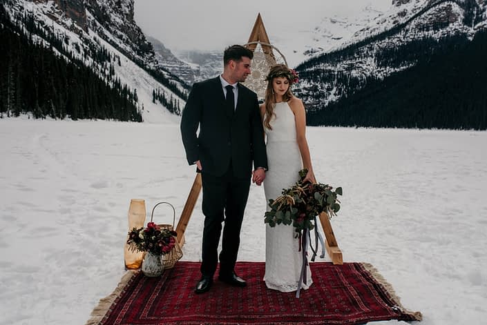 bride and groom at lake louise in winter photoshoot with burgundy rug and boho style backdrop accented by eucalyptus and flowers