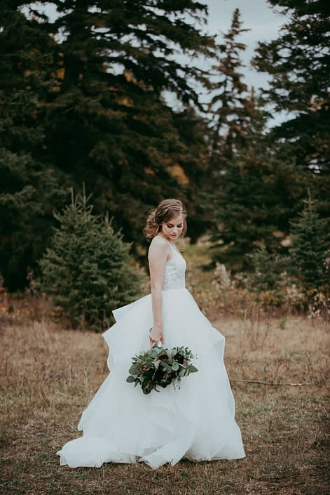 picture of bride with forest background and handkerchief skirt with bridal bouquet with red roses and burgundy dahlias and navy viburnum berries and mixed eucalyptus