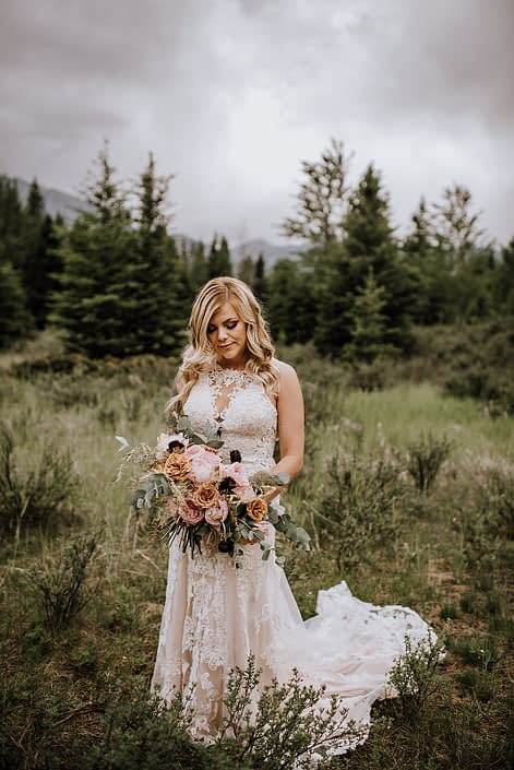 bride holding organic bridal bouquet of toffee roses, pink ohara garden roses and cinerea eucalyptus