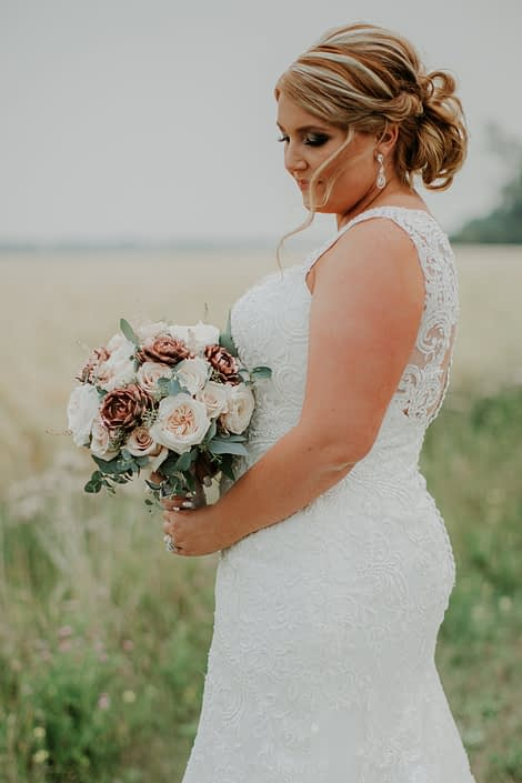bride with blonde updo and wedding dress holding a bridal bouquet designed with rose gold succulents, ivory garden roses and blush spray roses and eucalyptus