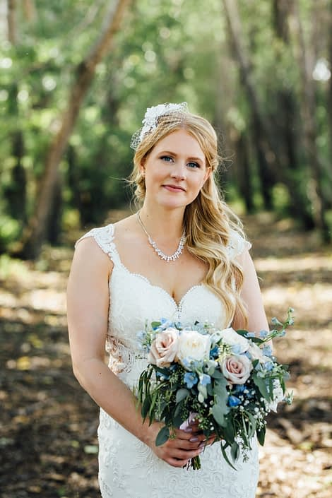 Kelsie wearing a vintage inspired birdcage veil and holding a blush and blue bridal bouquet featuring blue delphiniums, quicksand roses, white o'hara garden roses, succulents, babies breath and eucalyptus greenery.