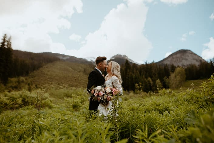 Bride and groom among the ferns with a pink and white bridal bouquet designed with peonies, tulips, roses and eryngium