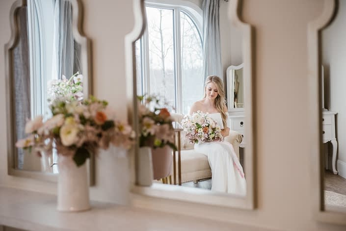 Bride in mirror holding pink and white bridal bouquet at Hilltop Wedding Centre