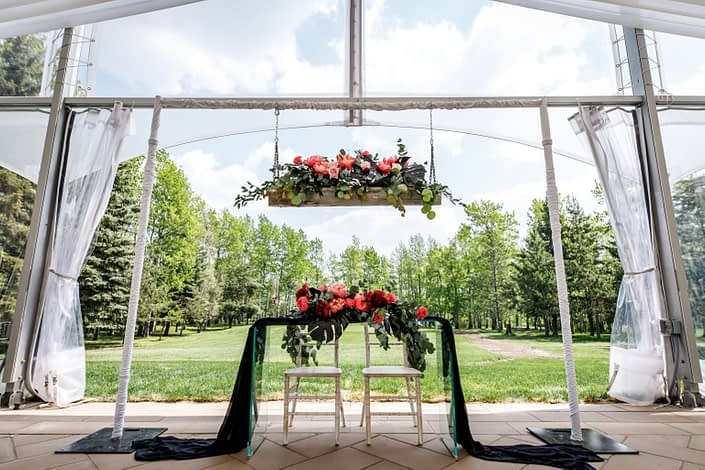 clear wedding tent at Hilltop Wedding center sweetheart table of clear glass with black voile runner and fresh floral arrangements designed with black monstera leaves, coral charm peonies and burgundy peonies
