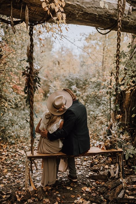 Couple kissing on a swing in the woods
