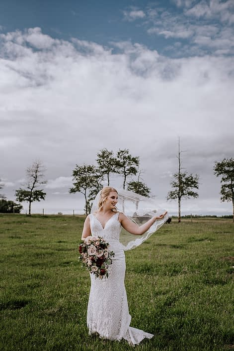 Bride standing in a field fanning her veil and holding a rustic red and blush bridal bouquet featuring quicksand roses, red charm peonies, blush spray roses, burgundy astrantia, light pink astilbe and eucalyptus greenery.