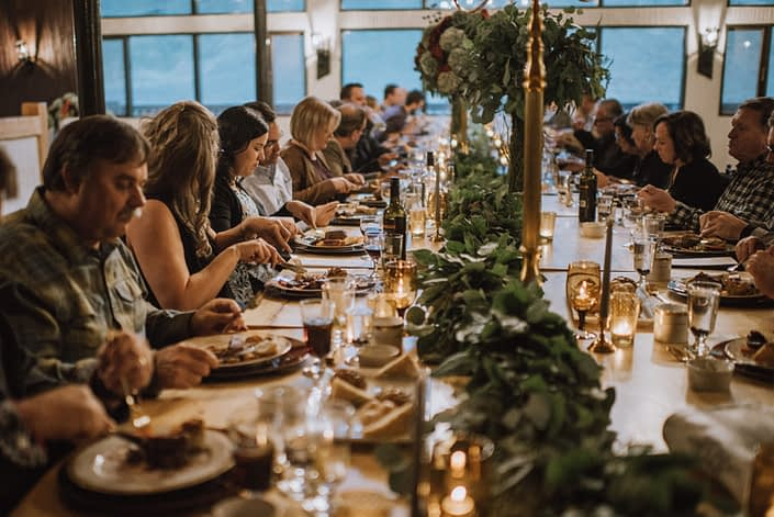 long table decor with mixed greenery garland and tall floral centerpieces on god candelabras at canyon ski resort in red deer alberta