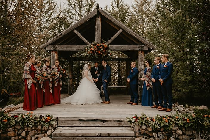 Hayley and James' rustic fall wedding ceremony featuring archway arrangement, garlands, bouquets and boutonnieres.