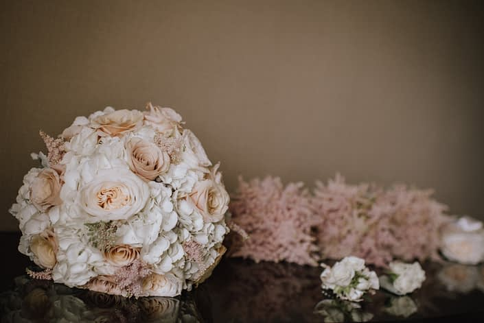 bridal bouquet designed with white hydrngea and white ohara garden roses and quicksand roses and pale pink astilbe with bridesmaids bouquets of pale pink astilbe and corsages and boutonnieres