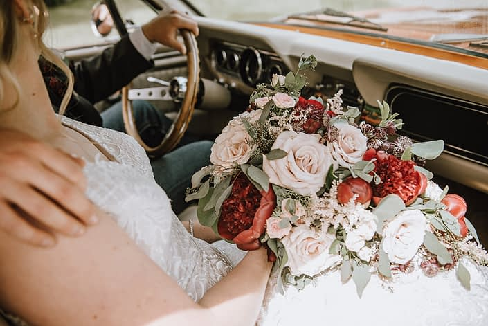 Bride and groom in an antique car holding a rustic red and blush bridal bouquet featuring red charm peonies, quicksand roses, blush spray roses, burgundy astrantia, and light pink astilbe with eucalyptus greenery.