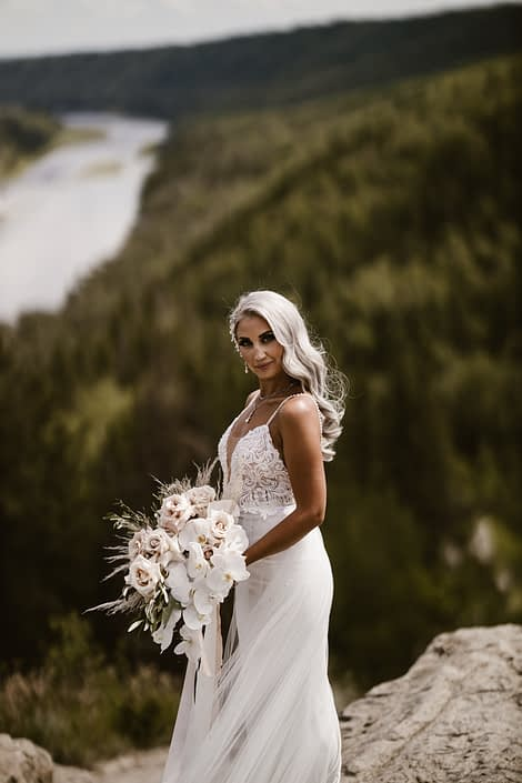 Bride, Sandra, holding her boho glam bouquet designed in a cascading style with quicksand roses, phalenopsis orchids, pampas grass, olive branches and silver dollar eucalyptus.