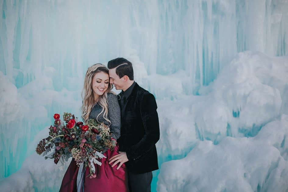 Bride and Grooms smiling for their engagement photoshoot at the ice castles in winter in edmonton alberta with a bridal bouquet of tulips, frittilaria and helleborus