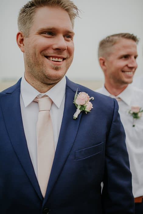 Groom in navy suit with blush tie and spray roses