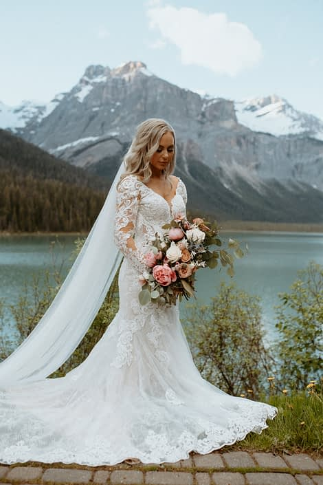 Bride holding pink and white bridal bouquet designed with peonies, roses, eryngium and tulips with a view of Emerald Lake and the Rocky Mountains