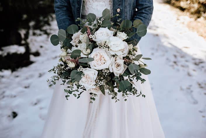 bride holding bouquet of playa blanca and quicksand roses, waxflower and eucalyptus