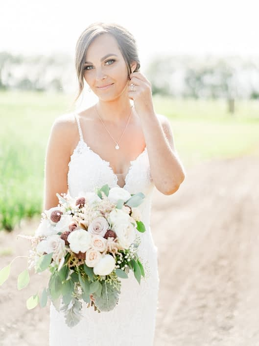 Bride, Taryn, wearing a white lace gown and holding a bouquet made with dusty pink amnesia and quicksand roses, white o'hara garden roses, rose gold painted scabiosa pods, ranunculus, astilbe, babies breath, dusty miller, and eucalyptus.
