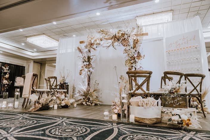 Down the Aisle Wedding Show 2020 Calyx Floral Design booth decorated with gold painted monstera leaves, painted sago palm, pampas grass, playa blanca roses, quicksand roses and other dried foraged leaves and branches.