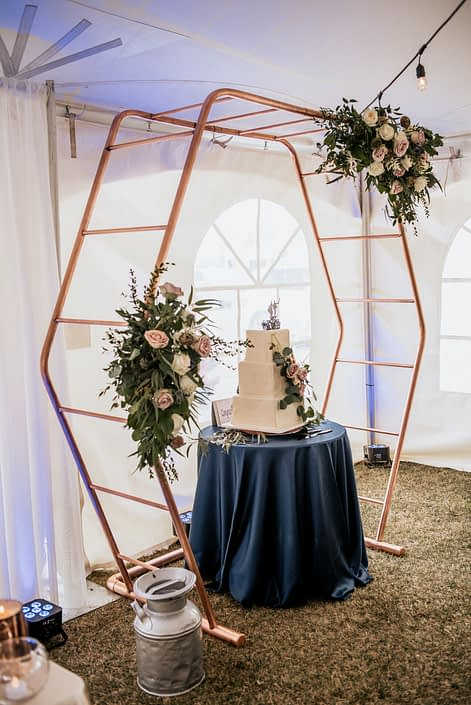 Copper hexagon decorated with mauve and navy floral arrangements with a flower covered wedding cake