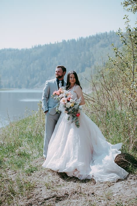 Bride and groom standing beside a river holding a crescent shaped bouquet featuring coral charm peonies, quicksand and playa blanca roses, peach ranunculus, pale pink astilbe, silver plumosa and a mixed variety of eucalyptus greenery.