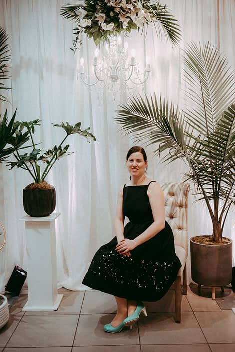 Travis Mills owner of Calyx Floral Deisgn in front of white backdrop with chandelier and floral arrangements and tropical plants at grand opening