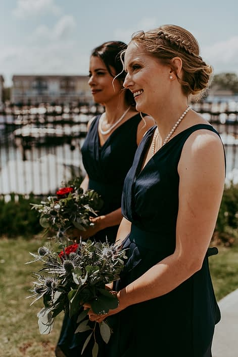 Tanya and Sean's RCMP wedding bridesmaids wearing navy blue and holding bouquets made of black baccara roses, eryngium and eucalyptus