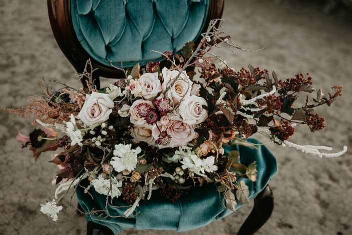 teal vintage chair with a bridal bouquet designed with burgundy astrantia, white scabiosa, white amaranthus, twigs and blush roses