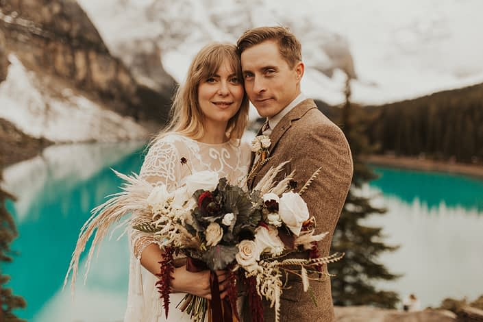 Moraine Lake Elopement Styled Shoot - male model wearing ivory boutonniere, brown jacket and bolo tie. Girl wearing ivory lace bridal gown while holding pampas grass bouquet with blush roses and pops of red flowers