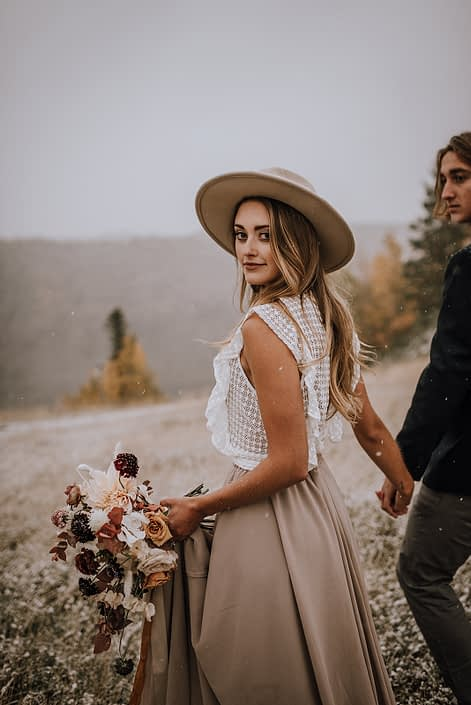 couple walking with a neutral coloured fall bouquet through a field with snow