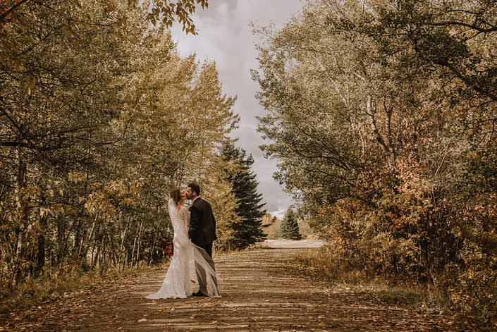 Bride and groom kiss on the path at Canyon Ski Resort in the autumn