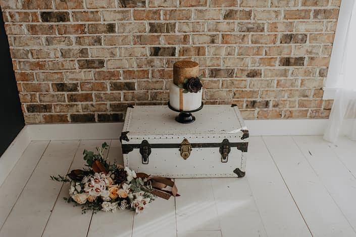 Neutrals Styled Shoot with Down the Aisle - Neutral coloured bouquet of orchids, roses, magnolia leaves and eucalyptus greenery beside a vintage trunk with a cake on top.