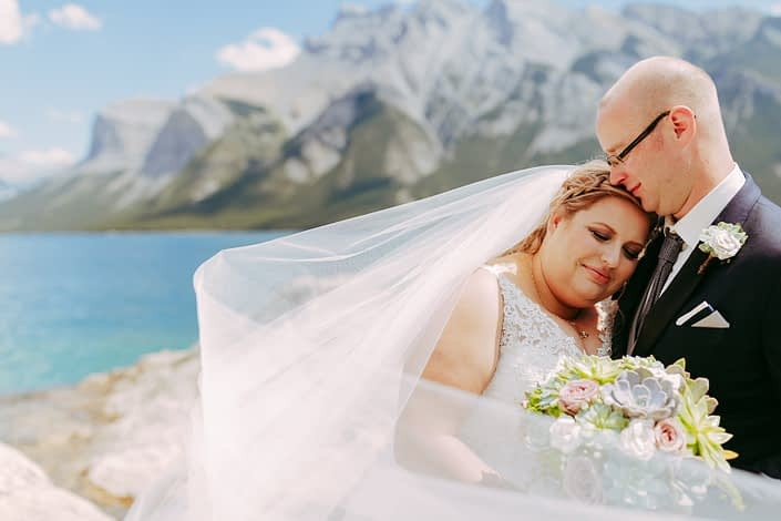 Bride and groom with veil in front of a lake in the summer with a succulent boutonniere and bridal bouquet