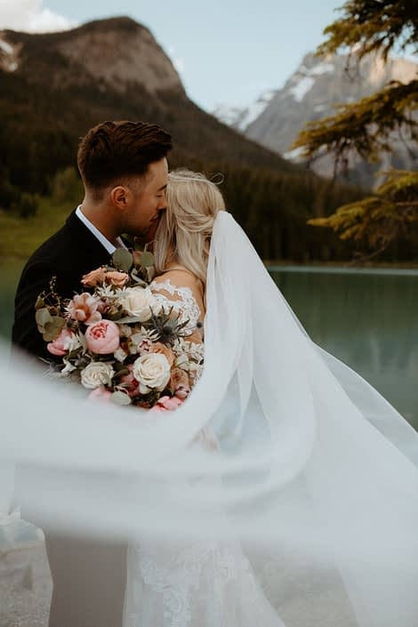 Bride and groom with windswept veil and pink and white bridal bouquet featuring peonies, roses, tulips and eryngium with eucalyptus greenery