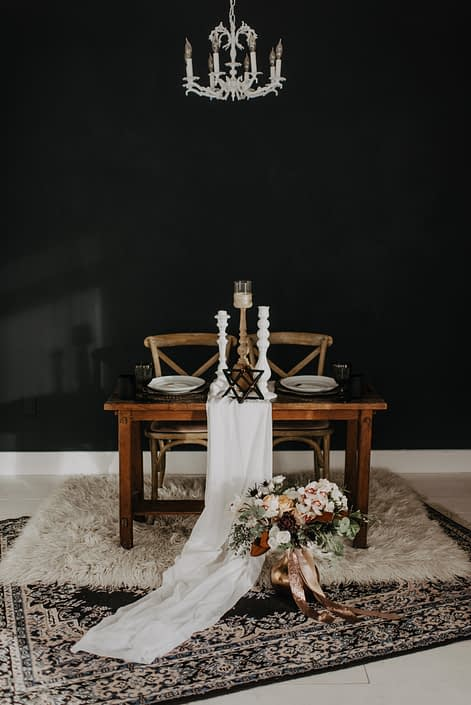 Neutrals Styled Shoot with Down the Aisle - Neutral coloured bridal bouquet with roses, orchids, magnolia leaves and eucalyptus greenery tied with trailing ribbons next to a decorated sweetheart table.