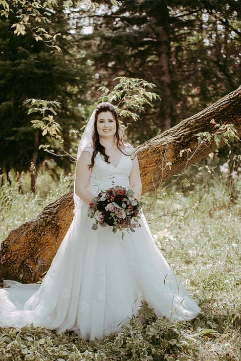 Bride with rustic burgundy and dusty rose bridal bouquet featuring roses, dahlias, ranunculus and lisianthus