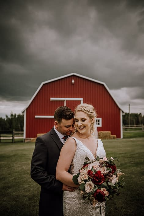 Bride and groom, Courtney and Caleb, in front of a red barn with grey clouds overhead; rustic red and blush bridal bouquet designed with red charm peonies, quicksand roses, burgundy astrantia, pale pink astilbe, and blush spray roses with eucalyptus greenery.