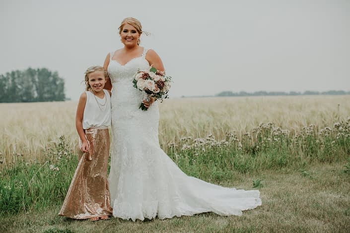 bride and flowergirl in rose gold sequin skirt and white top with bridal boqueut of rose gold succulents and ivory and blush roses and eucalyptus