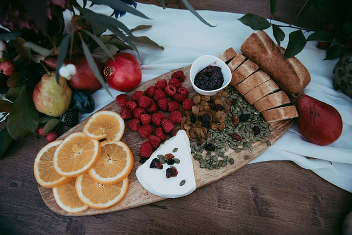 Charcuterie board on harvest table with blush silk runner and fresh fruit and berries and cheese and sunflower seed and bread