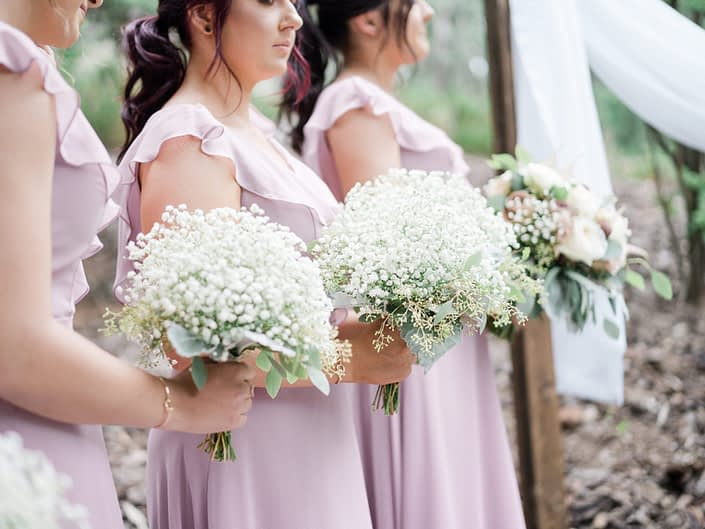 Bridesmaids wearing dusty rose gowns and holding gyposphelia (babies breath) bouquets.