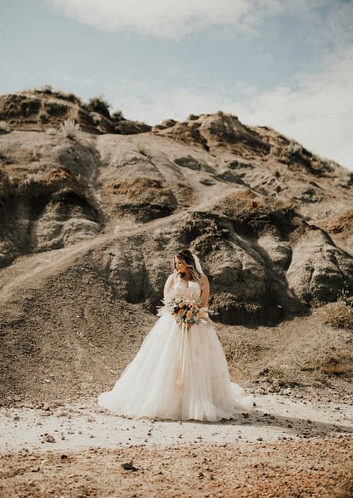 Boho Bride, Lizelle, in the Drumheller desert with peach and burgundy boho bouquet