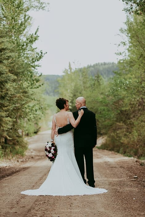 Bride and groom walking with arms around each other while bride holds an elegant pink and burgundy bouquet featuring helleborus, Sarah Bernhardt peonies, ranunculus, Black Bacarra Roses, Blackberry Scoop plum scabiosa, tulips, astrantia and eucalyptus.