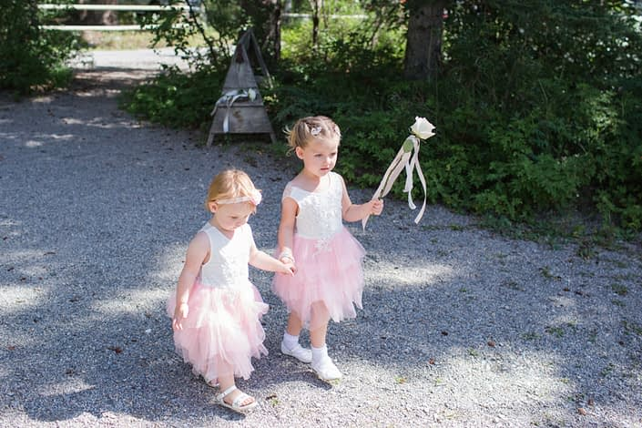 Flower girls carrying a white o'hara garden rose with pale pink trailing ribbon for Amy and Kerry's Pink and Blue Canmore Wedding.