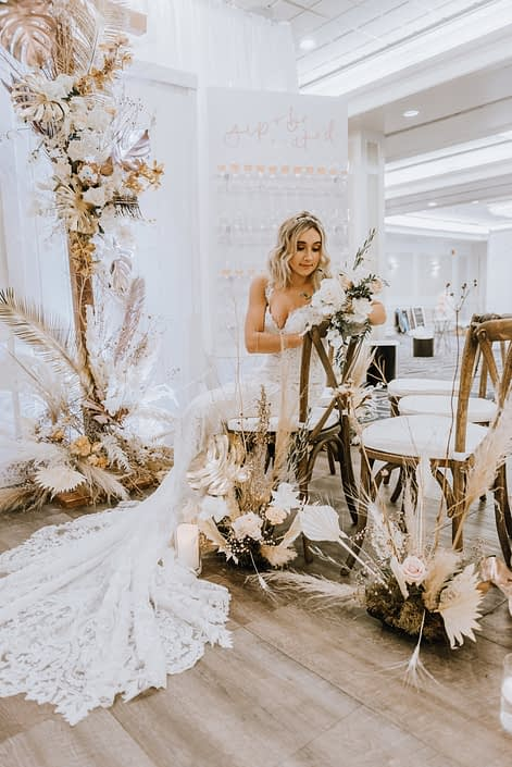 Model at the Down the Aisle Wedding Show holding a white and blush bouquet with roses, Japanese sweet peas and eucalyptus greenery surrounded by arrangements made of blush pink roses, gold painted monstera leaves, pampas grass and dried leaves and branches.