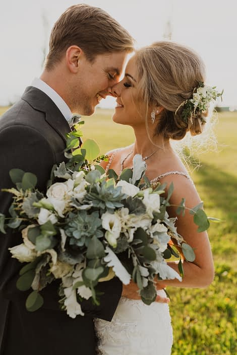 Leah and Chance; white and grey green bridal bouquet with a vintage feel designed with Playa Blanca roses, lisianthus, astilbe, dusty miller, blue star succulents, and a mixed variety of eucalyptus greenery; bride hair flowers.