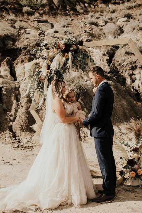 Bride and groom in front of outdoor ceremony wooden archway covered with boho floral arrangements