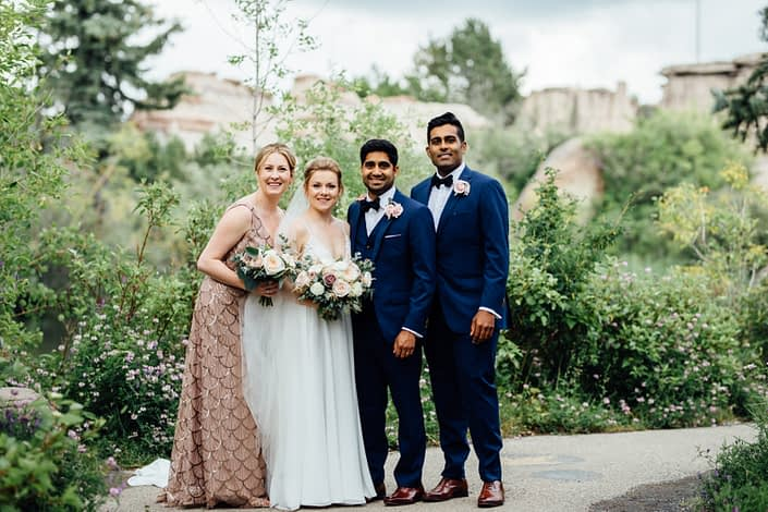 Jill and Jason's bridal party at the Calgary Zoo; bride and bridesmaid holding bouquets made with quicksand roses, white o'hara garden roses, white ranunculus and light pink astilbe finished with eucalyptus greenery; groom and groomsman wearing blush pink boutonnieres made of spray roses and eucalyptus.