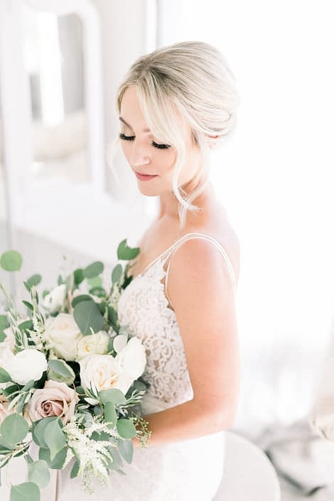 Close-up of Kayla holding her bridal bouquet designed with white o'hara garden roses, white ranunculus, quicksand roses, white astilbe, olive branches and fresh eucalyptus.
