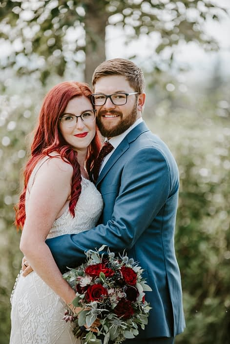 Hailey and Brandon embracing with a burgundy bridal bouquet with royal blue accents